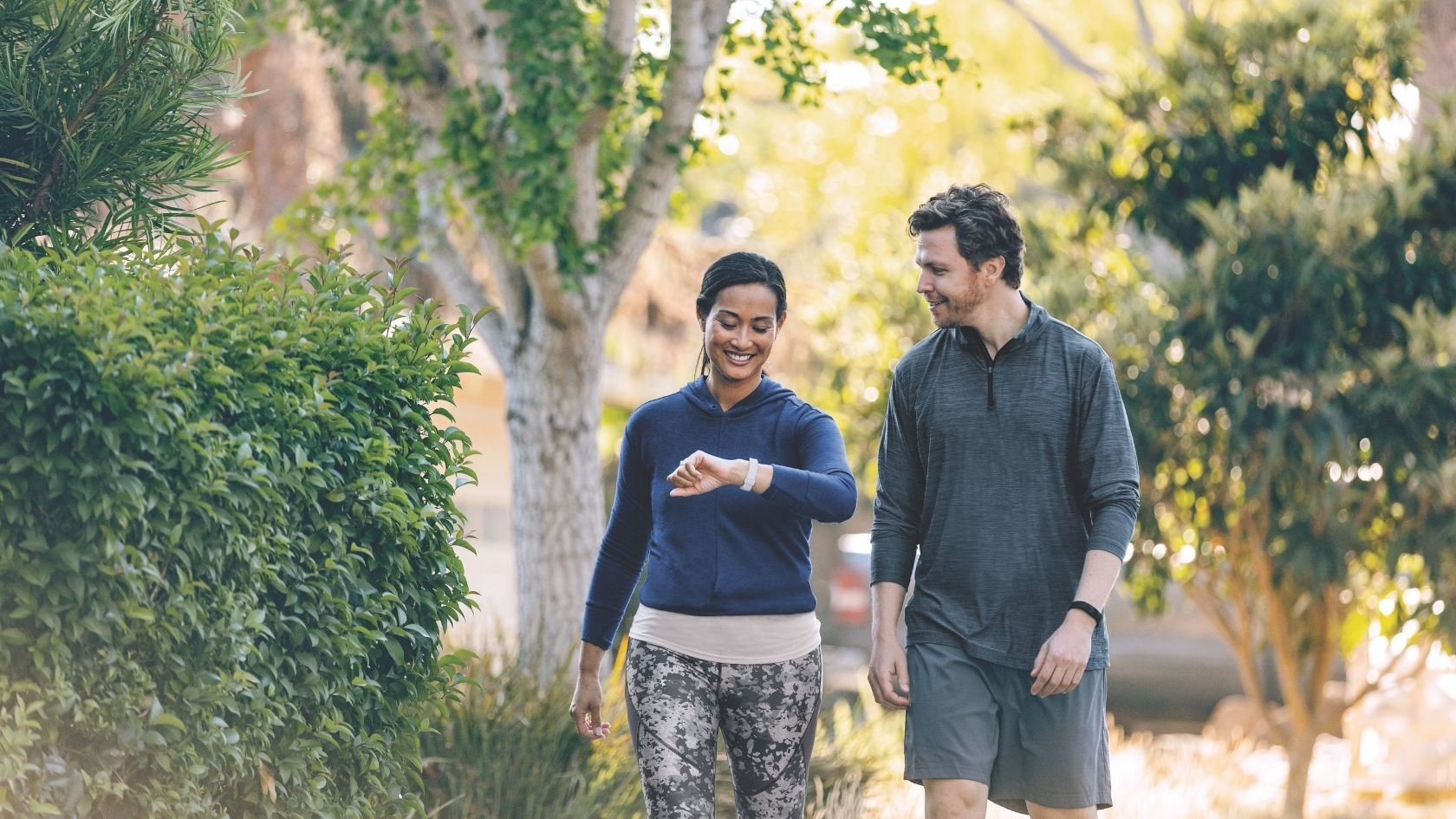 A man and a woman take a walk while tracking their fitness on their Fitbit Inspire 2