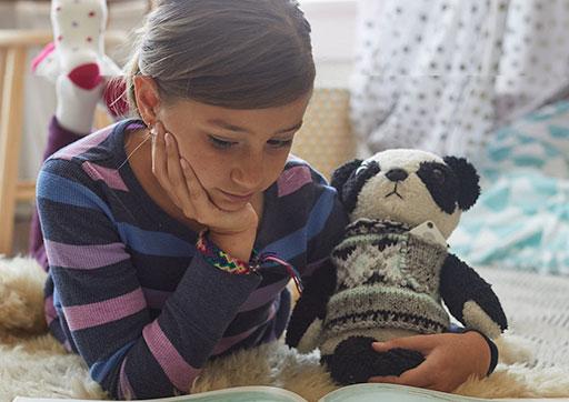Girl with stuffed animal with Tile on it